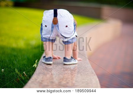 small boy in shorts on suspenders and sneakers climbed onto a shiny granite parapet in the park and turned his booty getting on all fours