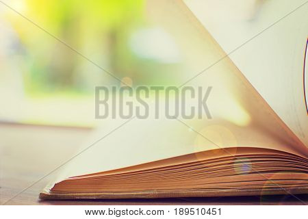 Open hardback book on wooden table with blurred backdrop. copy space for text. selective focus.