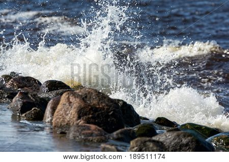 Sea waves breaking on a stone, forming a splash