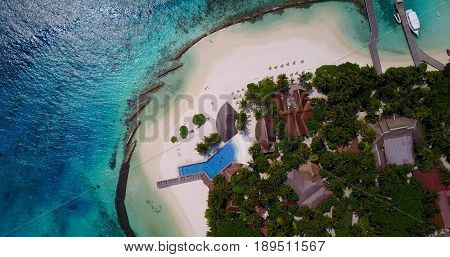 Aerial flying drone view of Maldives white sandy beach luxury 5 star resort hotel water bungalows relaxing holiday vacation on sunny tropical paradise island with aqua blue sky sea ocean 4k.