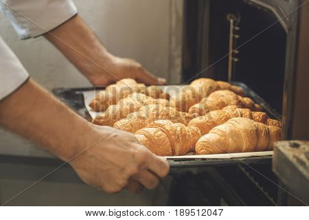 Bakery chef cooking bake in the kitchen professional holding croissants