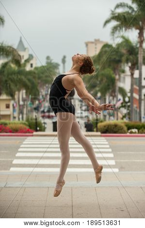 Beautiful and young ballerina leaping to left above downtown Ventura.