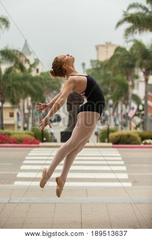 Beautiful and young ballerina leaping to right above downtown Ventura.