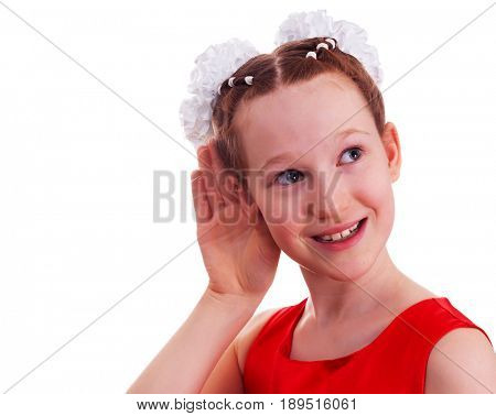 Kid girl in red dress listening with her hand on an ear, isolated on white background.