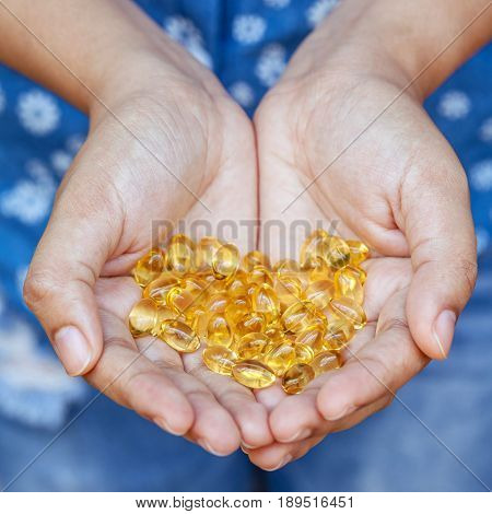 Handful Of Gel Capsules Of Omega 3. Close Up Capsules Of Fish Oil In Girl Hand. The Supplement High