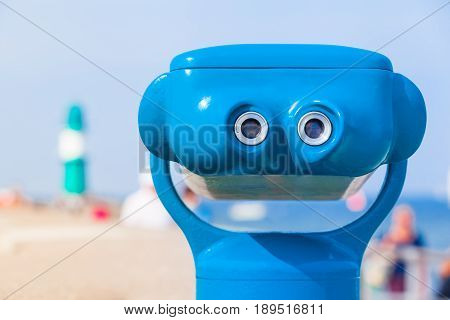 Ocular of blue telescope and beach background with lighthouse