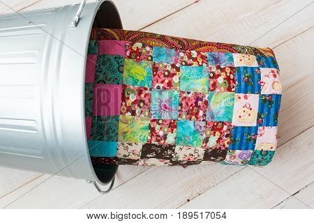 patchworking and fashion concept - colorful quilt in a metal bucket on a whitewashed wooden floor, close-up on patchwork product on a light background, side view