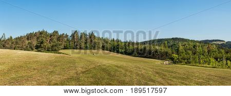 Panorama of a hilly forested landscape near the town of Tisnov in the Czech Republic. A sunny morning in the pasture
