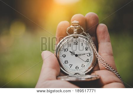 Hand holding retro stopwatch in natural background.