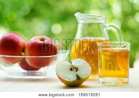 Apple juice in a jar and glass with sliced red apple, a bowl full of red apple in background