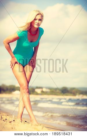 Being trendy and fashionable during summer vacation concept. Blonde slim attractive woman walking on beach wearing blue one piece swimsuit.