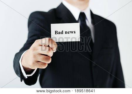 Businessman Holding Card With Word Bad News