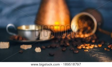 Coffee beans scattering off copper coffee pot, metallic coffee cup and brown sugar cubes on black slate surface