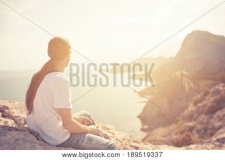 Hipster longhaired young man sitting on top of mountain looking on the beautiful view blue sea and mountains. Summer concept. Travel to Crimea Sudak. Copy space. Toned image. Selective focus poster