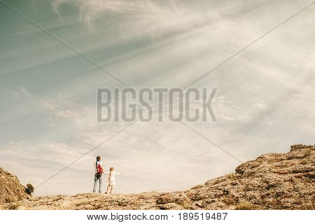 Small girl with father stay on the top of mountain looking on the beautiful view. Summer concept. Toned image
