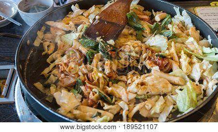 Korean spicy stir fried vegetable chicken and Korean spicy sauce (Gochujang) in big hot pan know as Dak Galbi