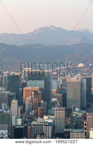 SEOUL SOUTH KOREA - NOV 03: Seoul city in the evening. Many buildings with beautiful mountain on November 03 2016 in Seoul South Korea