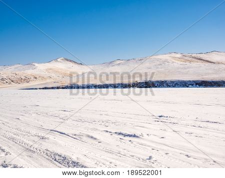 Wilderness of frozen water covered with snow in Lake Baikal near the snow mountain