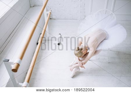 Young elegant and tired ballerina sitting on the white chair in the ballet room near the window. Poor girl in tutu is bent over her stretched legs. Top view