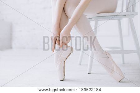 Young elegant classic dancer or ballerina sitting on the stool and stretching or warming up her feet with hands on by one not to hurt them during the dancing. Close up