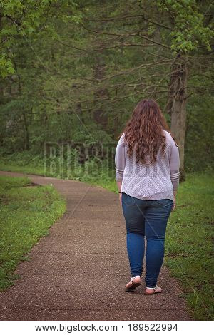 A woman walks down a path through a wooded area