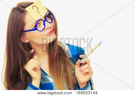 Woman confused thinking seeks a solution paper card with question mark on her head. Doubtful young female in glasses studio shot on white