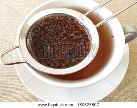 Loose honey bush tea in tea strainer
