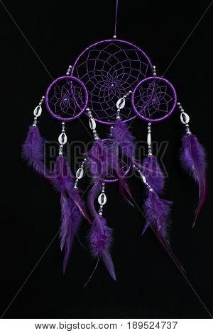 A dream catcher violet circles with feathers on black background