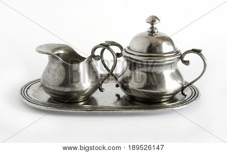 Antique pewter or silver creamer and sugar bowl on white background