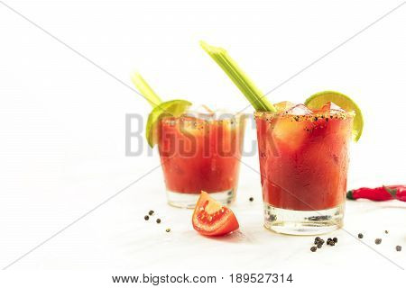 Bloody Mary cocktails with slices of lime, celery sticks, a piece of tomato, and copyspace