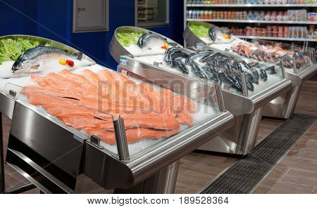 Fresh salmon, fillet and whole, on ice in a food store