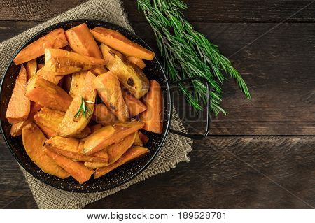 A square overhead photo of roasted sweet potatoes in a pan, shot from above on dark rustic wooden textures with rosemary branches, with a place for text