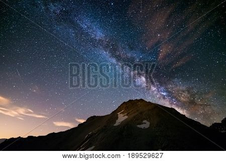 The colorful glowing core of the Milky Way and the starry sky captured at high altitude in summertime on the Italian Alps Torino Province.