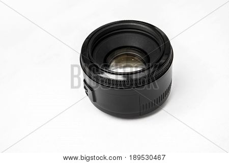 Close up of a black camera lens on the desk isolated on white background