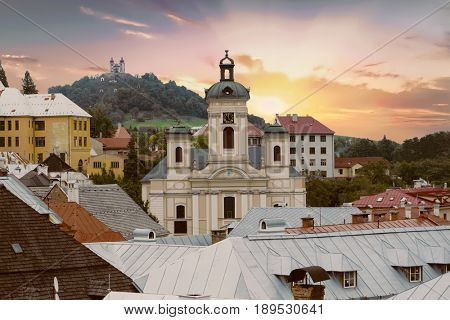 Old Slovakian mining town of Banska Stiavnica at dusk. The church of the Assumption of the virgin Mary is in front and calvary on the hill