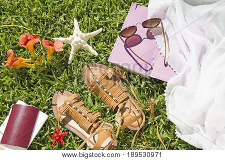 Summer and travel accessories on grass background