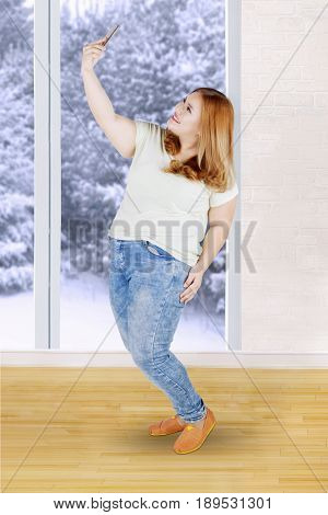 Full length of cheerful fat girl with blonde hair taking selfie photo with her mobile phone near the window at home