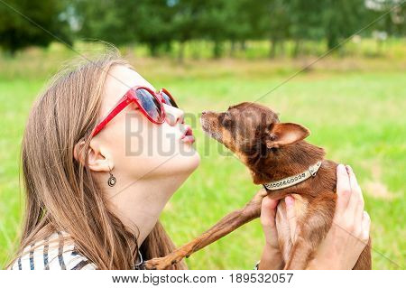 Unconditional love. Teenage girl kissing her little brown toy-terrier dog. Multicolored summertime outdoors horizontal image.