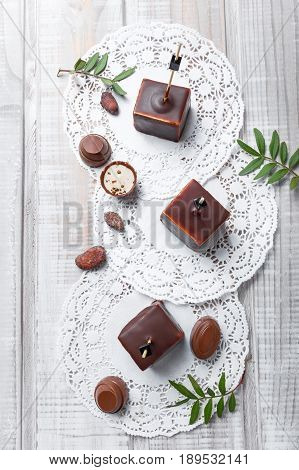 Chocolate souffle candy dessert with chocolate praline and cocoa beans on wooden background close up. Top view