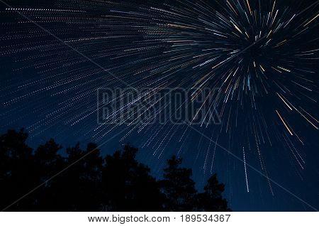 Beautiful night sky beautiful stars swirl above the trees, star trail vortex