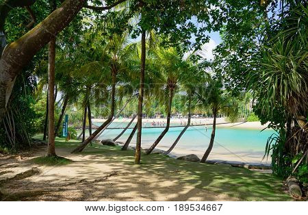Singapore, Singapore - February 13, 2017: People walk and relax at the sunny Palawan Beach of Sentosa Island in Singapore.
