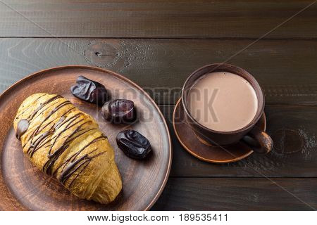 Hot chocolate or cocoa drink in cup and sweet croissant and dates fruit at plate on dark brown wooden table.