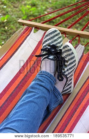 crossed legs in a colorful striped hammock wearing blue jeans and cloth shoes