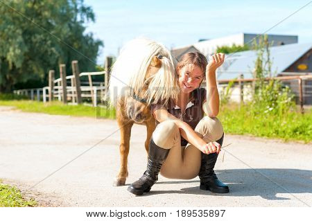 Lets play! Little playful shetland pony horse with his friend teenage girl.. Multicolored summertime horizontal outdoors image.