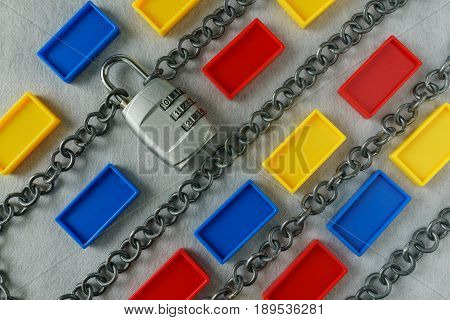 Chains with combination padlock and colorful plastic block as safety banking block chain concept.