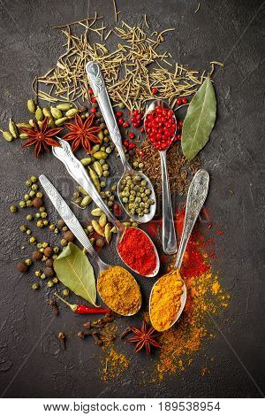 Variety Of Natural Spices, Seasonings And Herbs In Spoons On The Stone Table - Paprika, Curry, Coria
