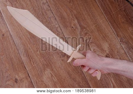 Hand hold wooden sabre, wooden floor visible on a background.