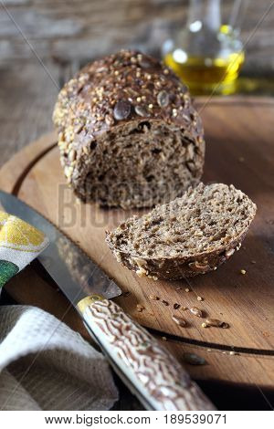 Rye french bread and olive oil on wooden chopping board