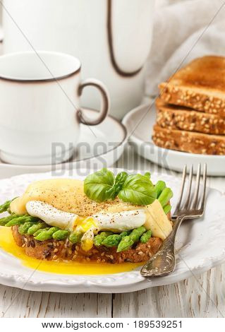 Bread Toast With Sesame And Flax Seed, Asparagus, Poached Egg And Hollandaise Sauce. A Traditional B