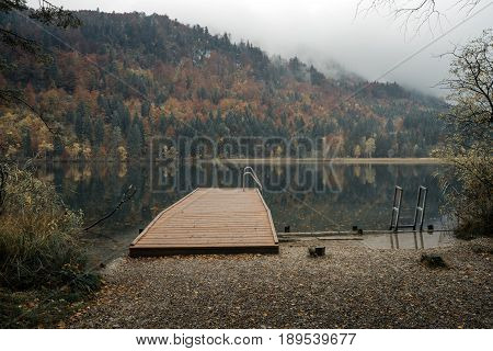 Fussen Bavaria Germany. Alpine Lake Schwansee near Hohenschwangau Castle and Neuschwanstein Castle. Cloudy autumn with rain. Autumn forest and beautiful view of the lake.